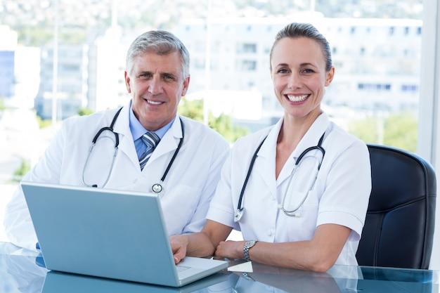 Улыбаясь врачей, работающих вместе на ноутбуке