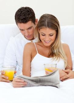 新聞を読んでオレンジジュースを飲む恋人