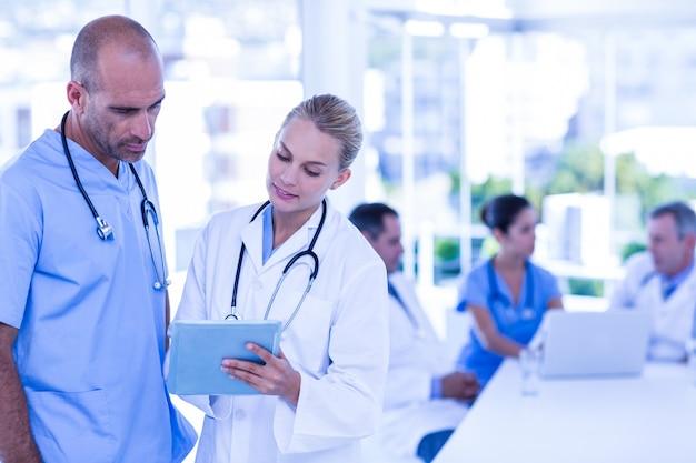 Два врача, которые смотрят в буфер обмена, а их коллеги работают
