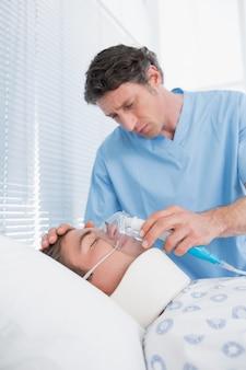酸素マスクを持っている医者