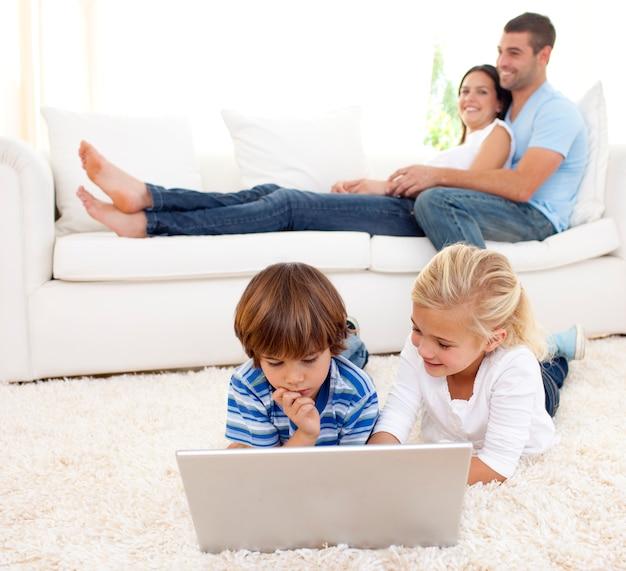 ラップトップと両親がソファに横たわっている子供たち