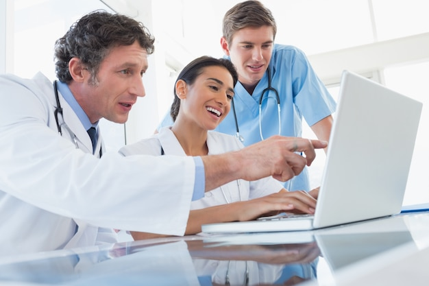Команда счастливых врачей, работающих на портативный компьютер