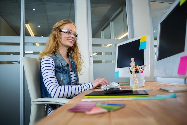 デザイナーが机に座ってキーボードを入力するのを笑顔で
