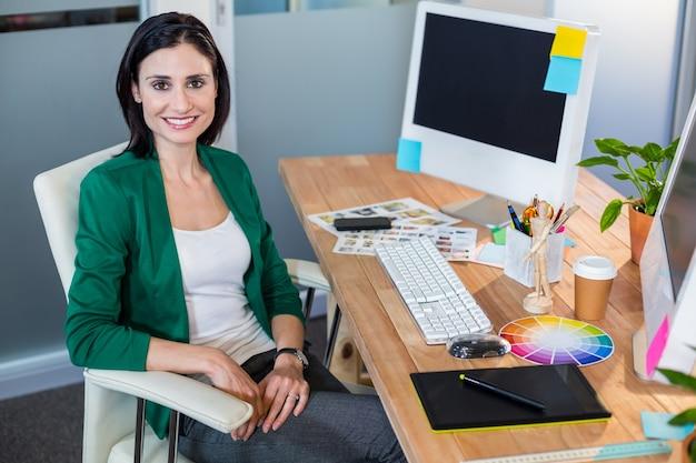 机に座っている笑顔のデザイナー