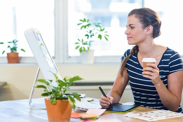 デジタイザーで仕事をしてコーヒーを持っている笑顔のカジュアル