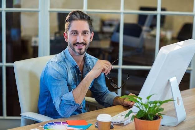 彼の机で働くカジュアルなビジネスマン