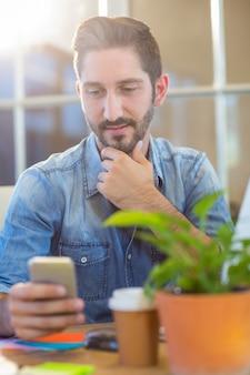 携帯電話でカジュアルなビジネスマンのメッセージ