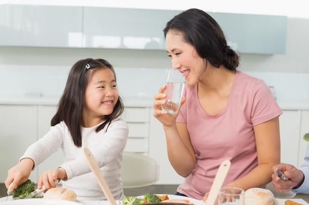 Маленькая девочка и мать едят пищу на кухне