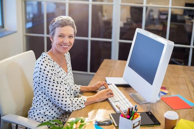 キーボードでタイピングしている笑顔のビジネスマン