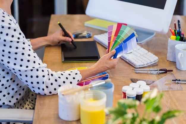 カラースワッチを見て、デジタイザで描画するカジュアルな実業家