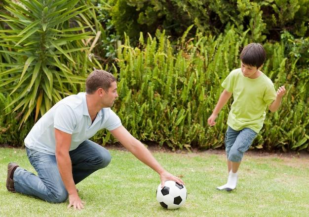 Сын играет в футбол со своим отцом