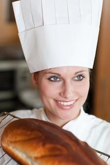 自信のある女性シェフのパンを焼く