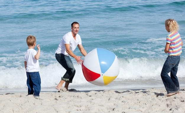 Счастливый отец и его дети играют с мячом
