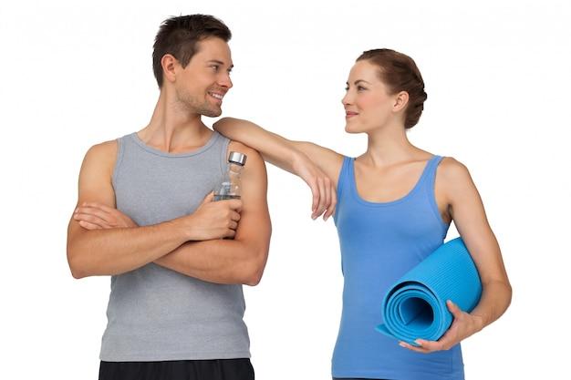 若いカップルと運動マットと水ボトルを合わせる