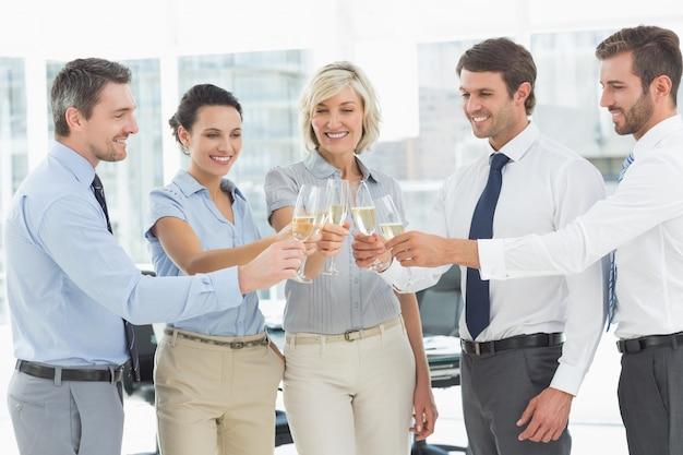 オフィスでシャンパンを焼くビジネスチーム