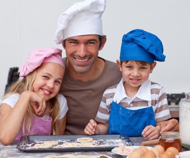 幸せな父と子供たちが一緒にクッキーを焼く