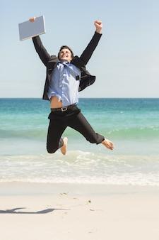 海の前でジャンプするビジネスマン