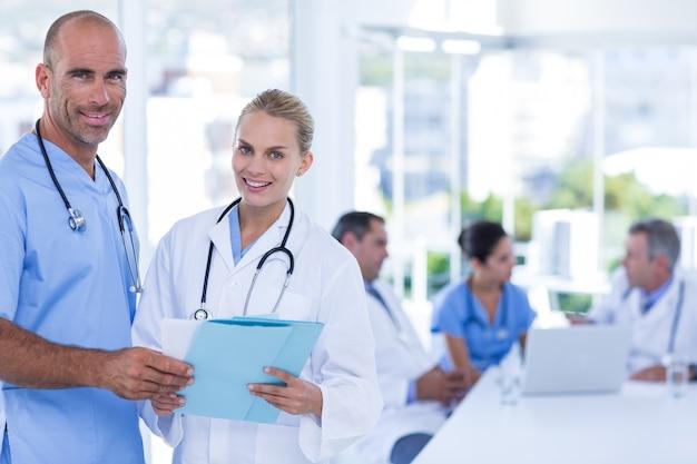 Два врача держат буфер обмена, а их коллеги работают