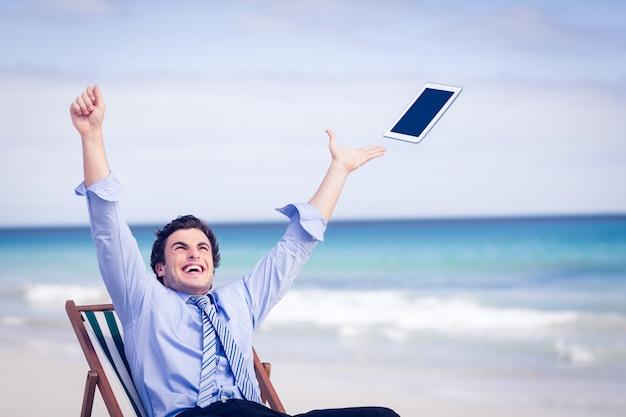 空中に彼のタブレットを投げつけている気さくなビジネスマン