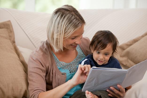 Мать смотрит на книгу с сыном