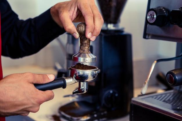 Бариста придает свежую кофейную гущу