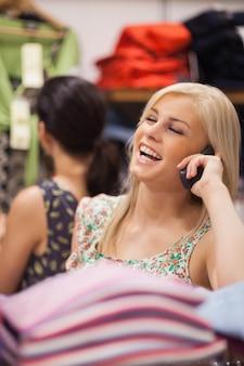 女性は笑いながら電話をかけている
