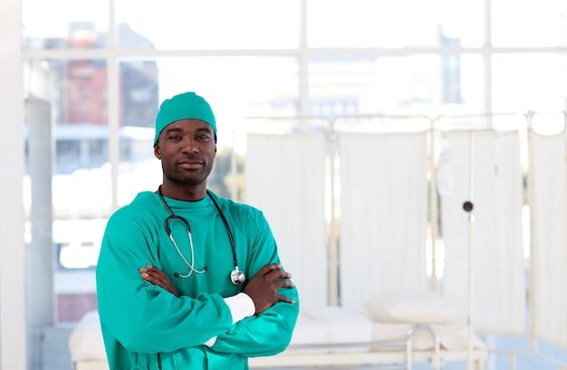 Серьезный афро-американский хирург со сложенными руками