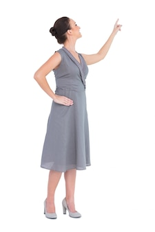 方向性を指摘する上品な服を着た豪華な女性を笑顔に