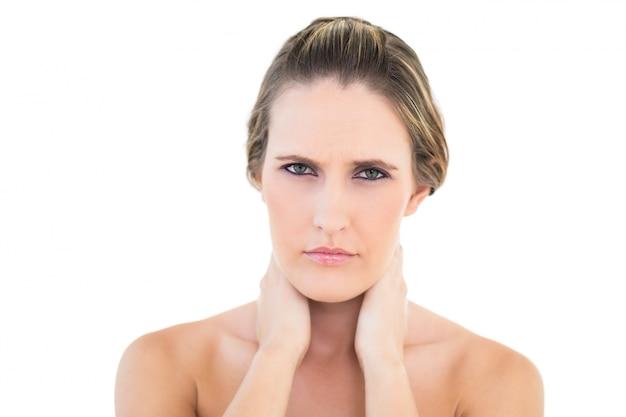 痛い首にカメラを見ている不満な女性