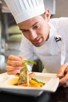 キッチン、料理を飾る集中的な男性のシェフ