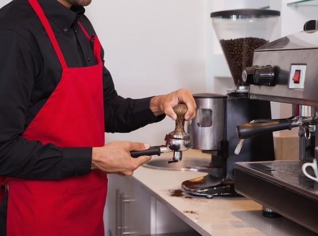 Бариста прижимает кофейную гущу