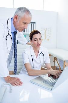 ラップトップと議論して仕事をしている集中した医療従事者