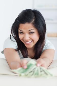 Улыбающаяся женщина с несколькими долларовыми купюрами