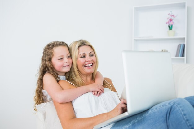 ラップトップで働く娘の抱擁の母