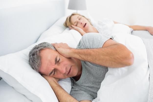 Усталый человек, блокирующий уши от шума жены, храпящей