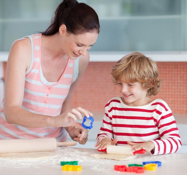 母親とクッキーカッターで笑顔の少年