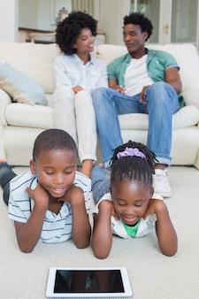Счастливые братья и сестры, лежащие на полу с помощью планшета