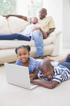 Счастливые братья и сестры, используя свой ноутбук
