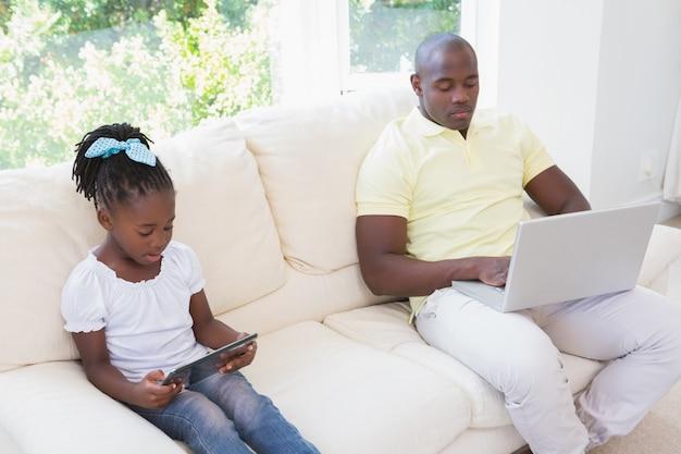 Счастливый отец, используя ноутбук и ее дочь, используя планшет на диване