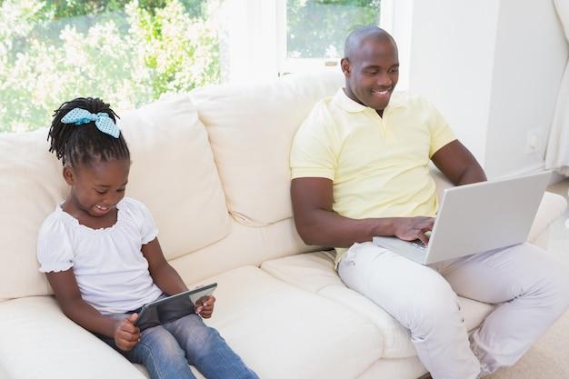 Счастливый улыбающийся отец, используя ноутбук и ее дочь, используя планшет на диване
