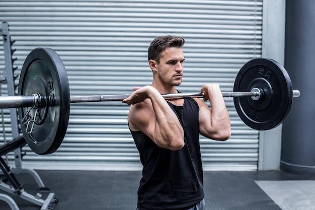 バーベルを持っている筋肉の男