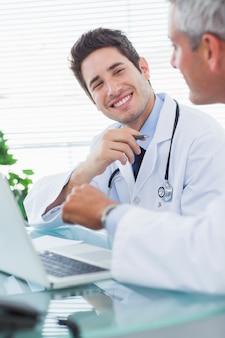 Улыбающиеся врачи, говорящие о чем-то на своем ноутбуке