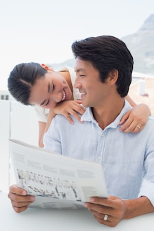 新聞を一緒に読んでいるカップル
