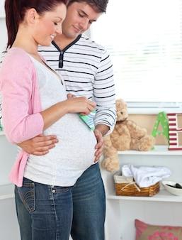 Улыбаясь беременная женщина с детской обуви, а муж, касаясь ее живот
