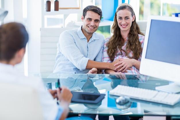 妊娠中の女性と夫はカメラで笑顔