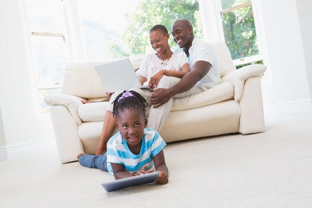 Довольно пара, используя ноутбук на диване и их дочь, используя планшет