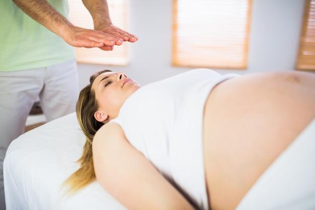 レイキの治療を受けている妊婦のビューを閉じます