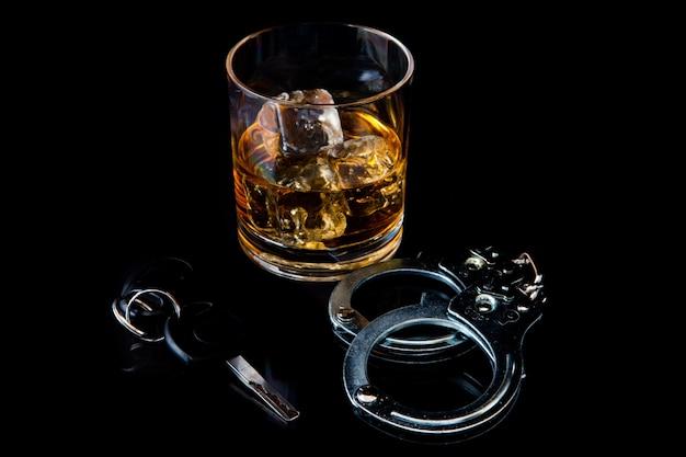 Виски на скалах с наручниками и автомобильным ключом