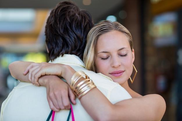彼女のボーイフレンドを抱き締める笑顔の女性が目を閉じた