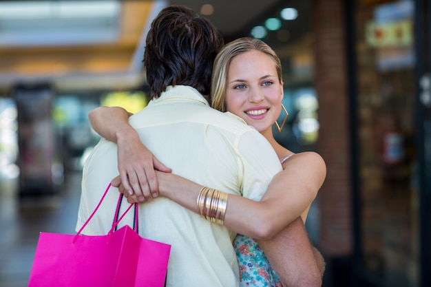 彼女のボーイフレンドを抱擁しているショッピングバッグで笑顔の女性